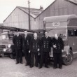 Group of firemen in front of fire engine