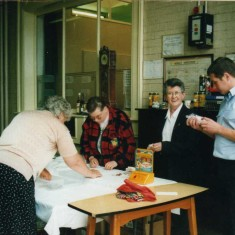 Marie, Pat and her daughter assist the leading fireman on the fire service benevolent fund table