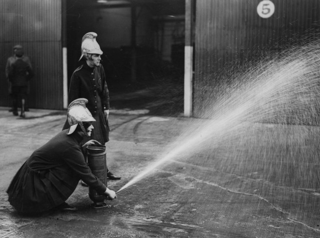 1928, Demonstrating the use of a portable fire extinguisher.