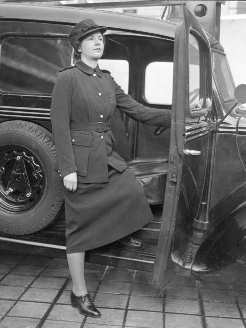 1938, a female firefighter models a new uniform.