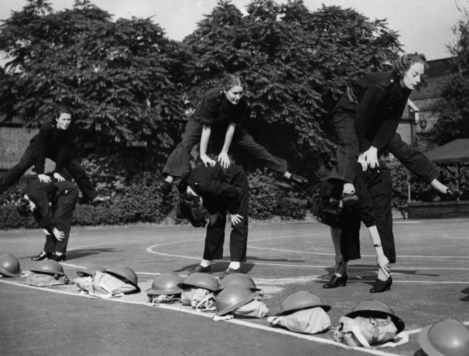 "1939, Group of Auxiliary Fire Service (AFS) women ""keeping fit"" with a game of leap-frog"
